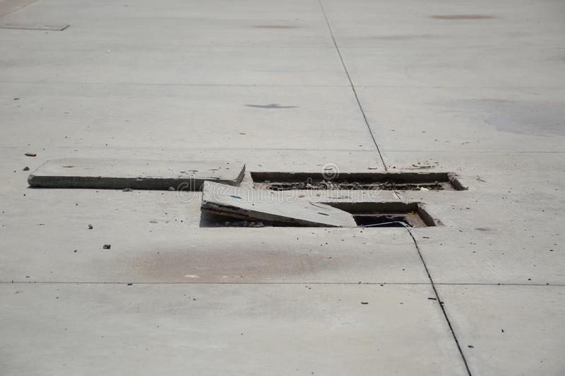 在街道的方形的形状水泥孔覆盖物 库存图片