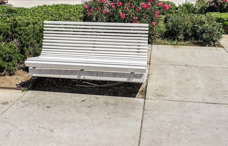 在街道的白色长凳 免版税图库摄影