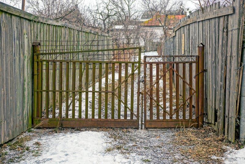 在街道的老生锈的门有木篱芭的 免版税库存照片