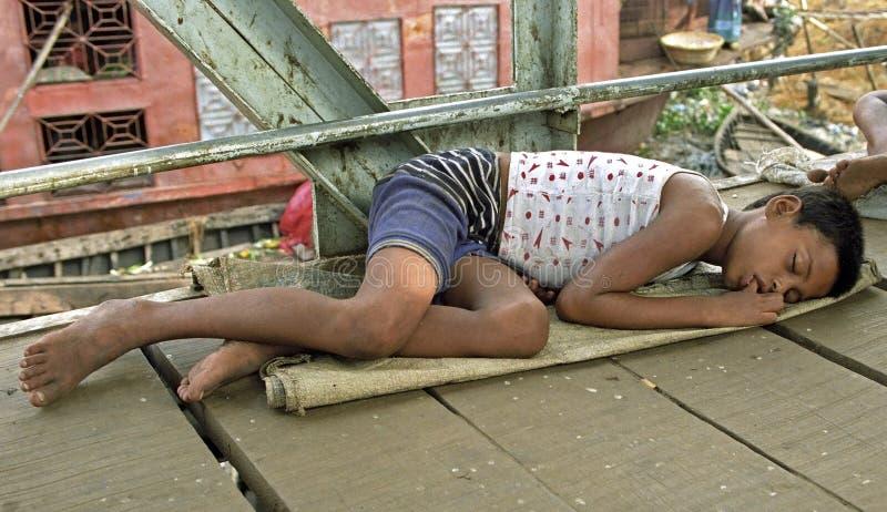 在街道睡觉的无家可归的男孩,街道孩子 免版税图库摄影