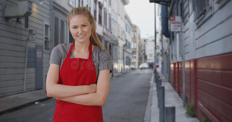 在街道胡同的迷人的年轻女性barista休假 库存图片