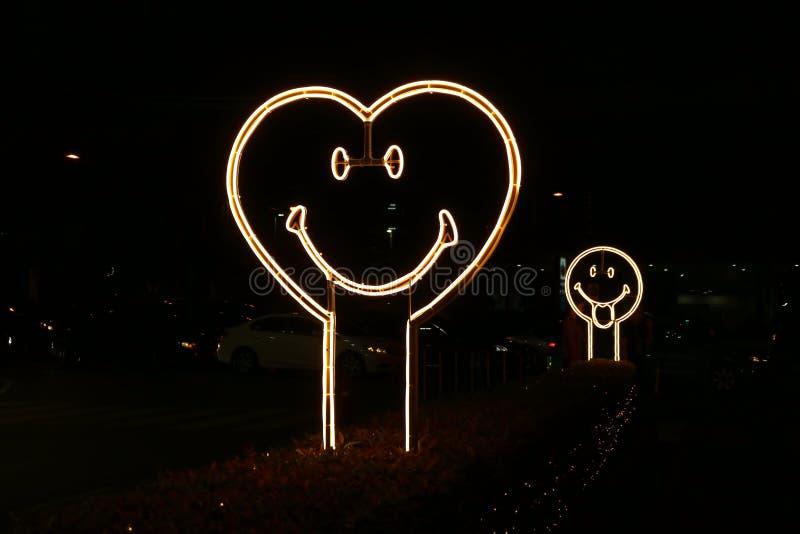 在街道边的心形的笑容霓虹灯标志在晚上 免版税库存图片