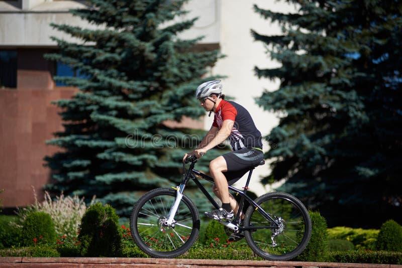 在街道边缘的男性骑自行车者训练 免版税库存照片