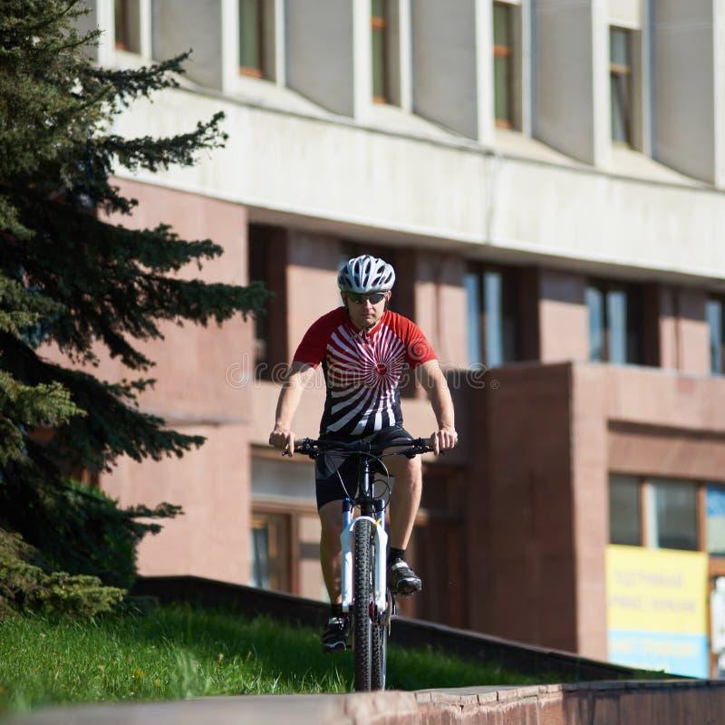 在街道边缘的男性骑自行车者骑马自行车 图库摄影