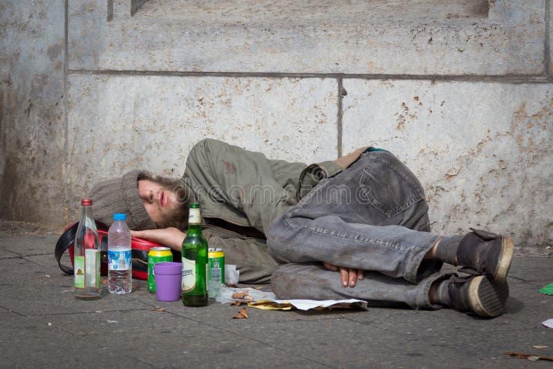 在街道边路喝的无家可归年轻酒精上瘾者说谎在柏林 图库摄影