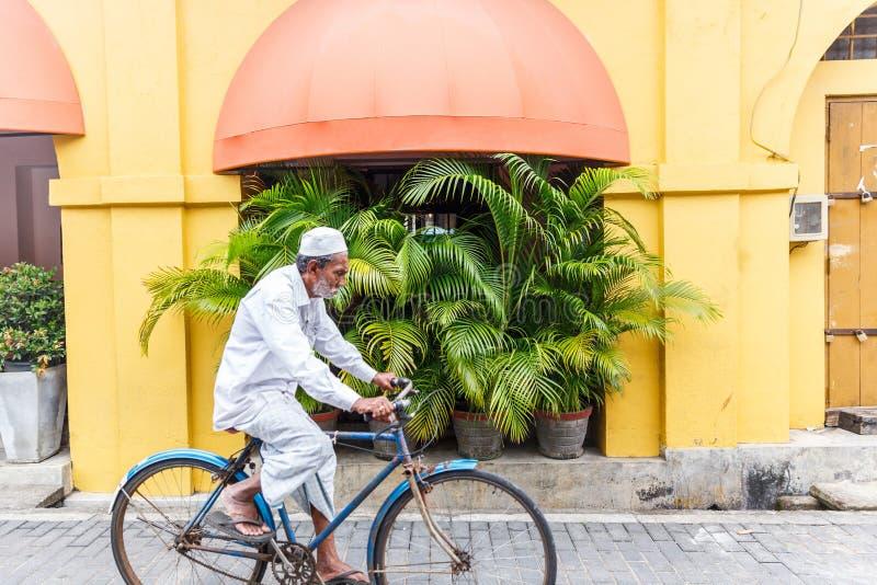 在街道,亚洲上的资深亚洲人骑马自行车 免版税图库摄影