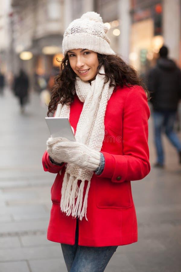 在街道-红色外套和羊毛盖帽的与智能手机的妇女和手套上的时尚在韩 免版税库存图片