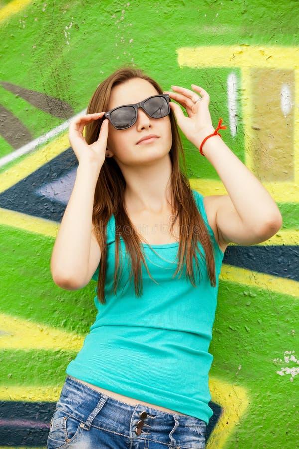 在街道画背景附近称呼太阳镜的青少年的女孩。 库存照片