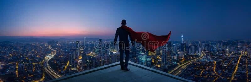 在衣服和海角英雄的商人站立在看起来伟大的都市风景的屋顶 免版税图库摄影