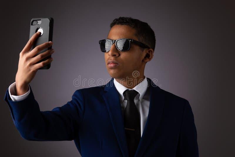 在衣服和采取与智能手机的Selfie打扮的西班牙男孩 库存图片