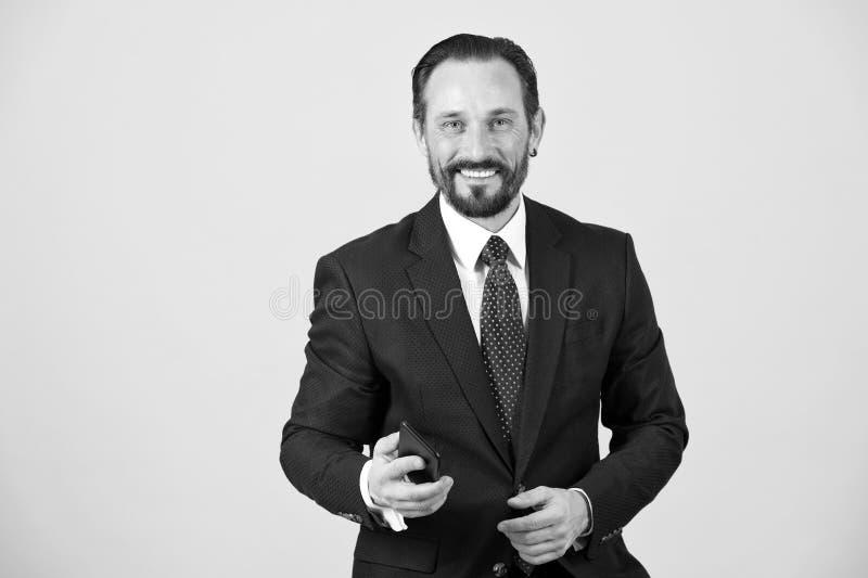在衣服和领带举行智能手机的微笑的和愉快的商人 免版税图库摄影
