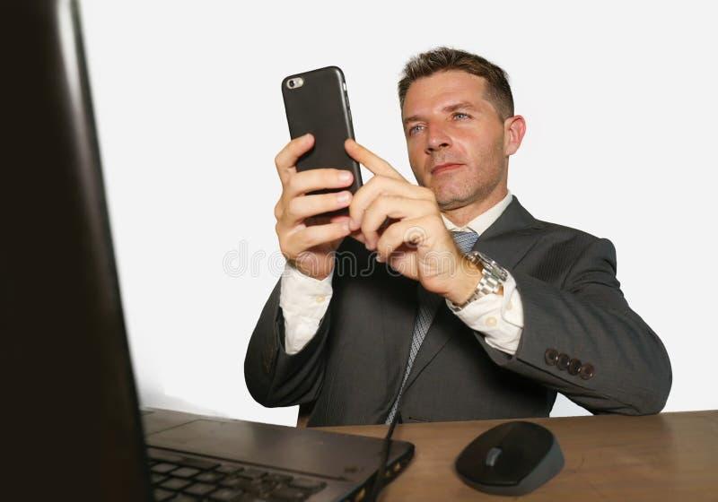 在衣服和领带工作的年轻可爱和愉快的商人在办公室使用手机的手提电脑书桌上在隔绝 免版税库存照片