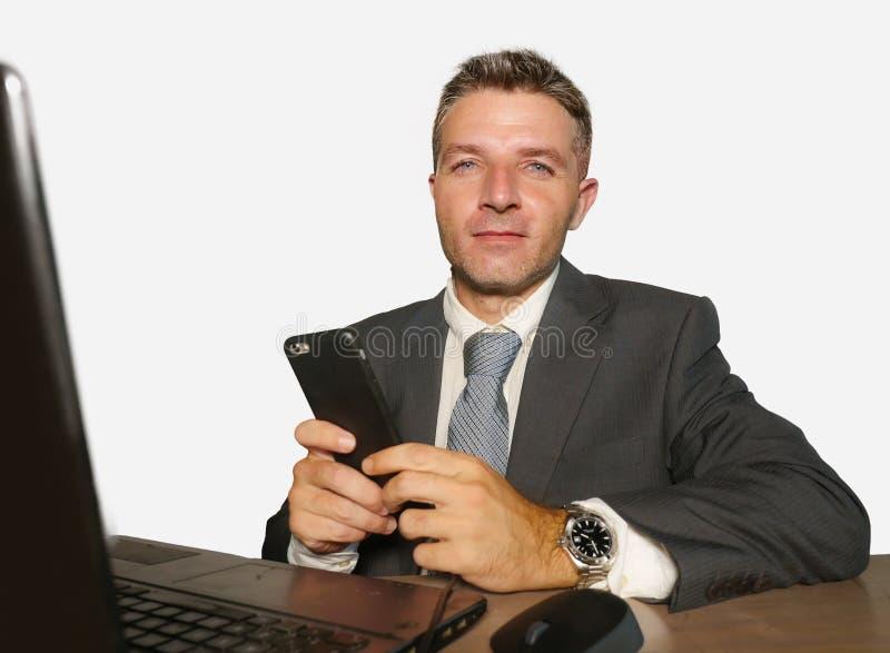 在衣服和领带工作的年轻可爱和愉快的商人在办公室使用手机的手提电脑书桌上在隔绝 图库摄影