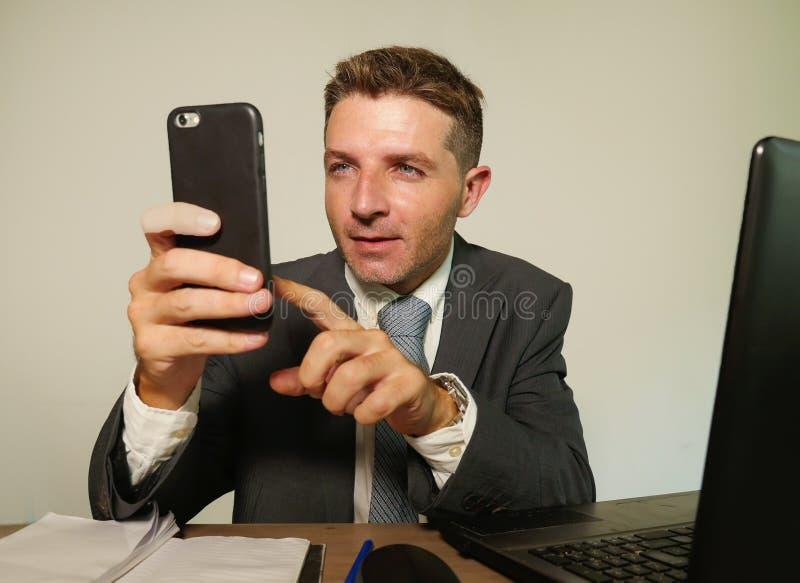 在衣服和领带工作的年轻可爱和愉快的商人在办公室使用手机的手提电脑书桌上在隔绝 库存照片