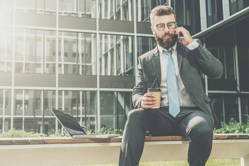 在衣服和领带的商人在他的手机外面坐长凳,饮用的咖啡并且谈话 附近膝上型计算机 图库摄影