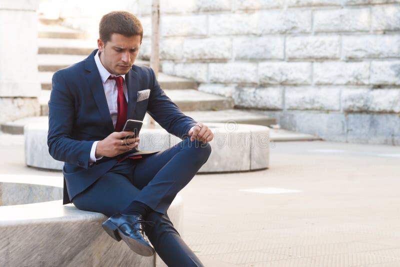 在衣服和领带的年轻商人咨询智能手机sitt 库存照片