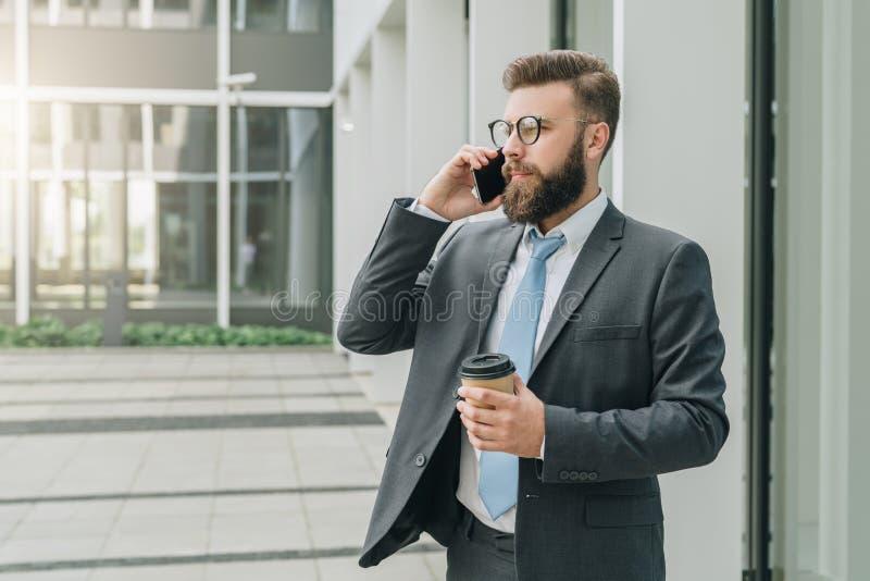 在衣服和领带的年轻商人在他的手机站立室外,饮用的咖啡并且谈话 人工作 图库摄影