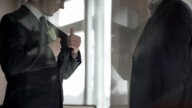 在衣服夹克,分享营业利润的两个伙伴的商人掩藏的金钱 免版税库存图片
