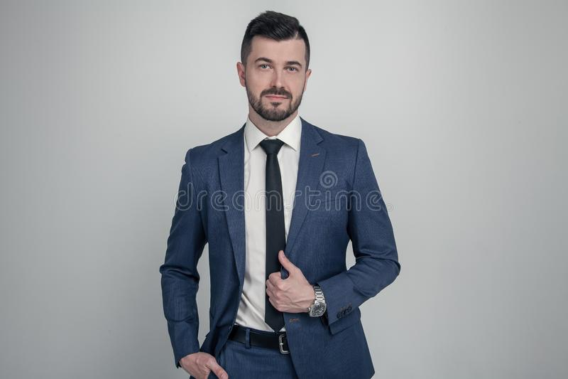 在衣服打扮的一个迷人的成熟的商业人的画象摆在,当站立和看照相机被隔绝在灰色时 免版税库存图片
