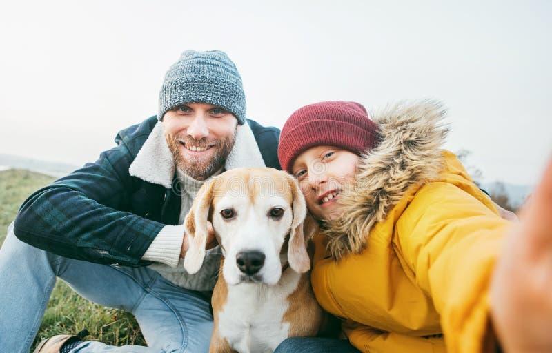 在衣服暖和和儿子打扮的父亲拍与他们的最佳的家人小猎犬狗的一张selfie照片 免版税库存照片