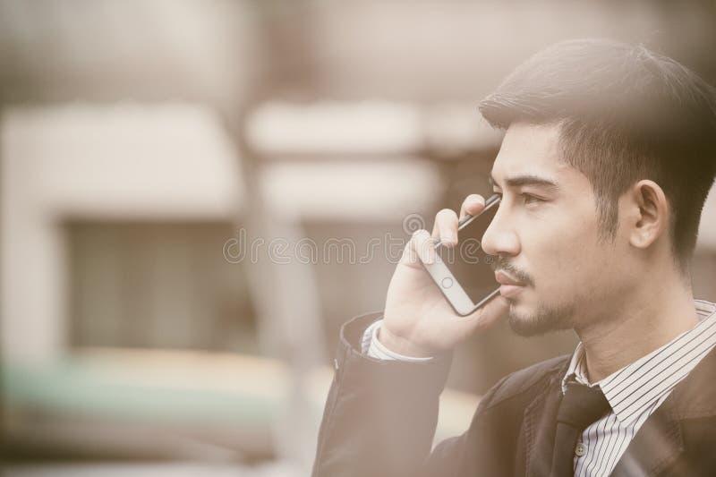 在衣服的严肃的年轻商人谈手机在城市 库存照片
