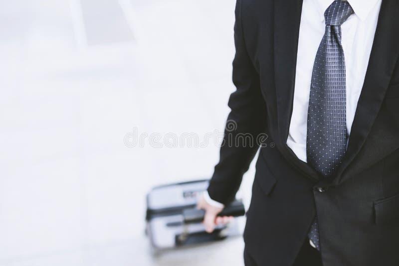 在衣服的商人走在与行李的公共交通工具大厦之外的在下班时间 拉扯手提箱的出差者在mo 库存图片