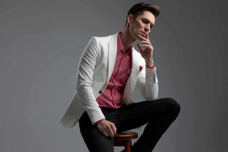 在衣服的安装的英俊的男性认为与手指的在嘴唇 免版税库存照片