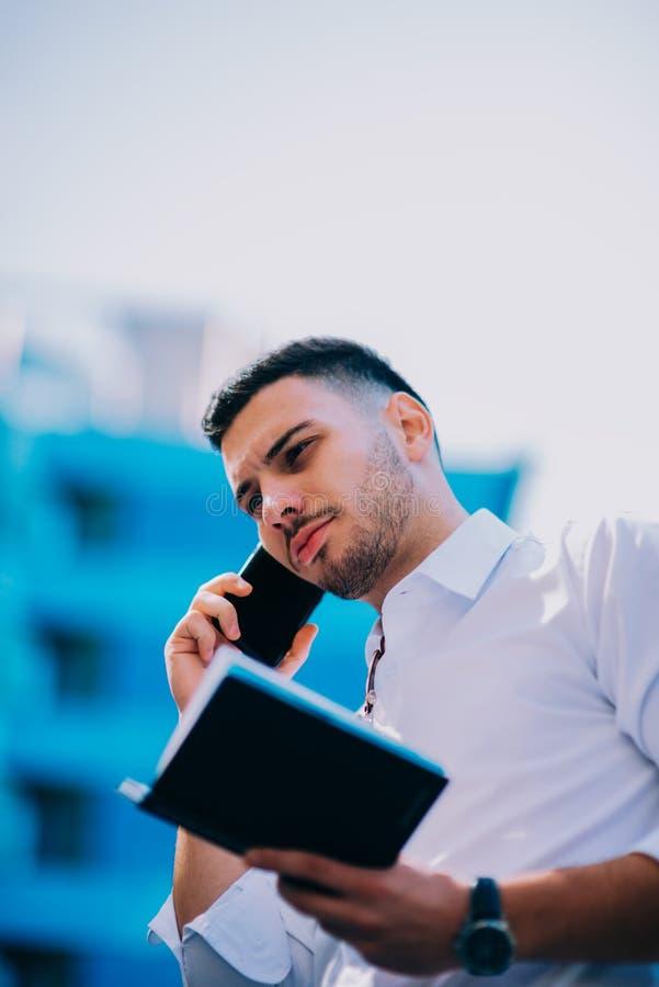 在衣服的年轻商人在他附近注视着财务c 免版税库存照片