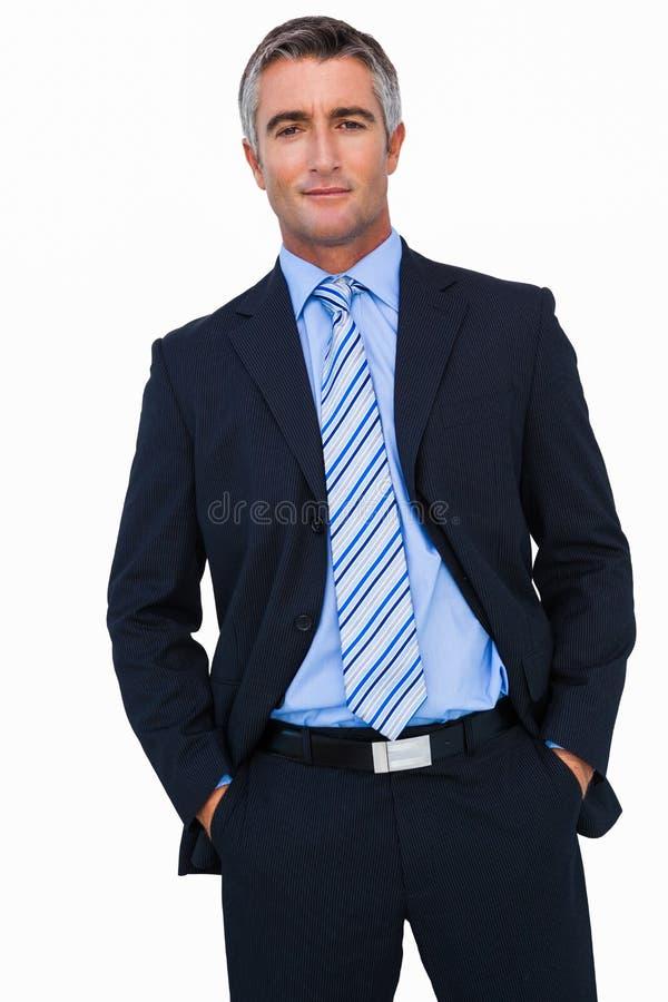 在衣服的微笑的商人用在口袋摆在的手 免版税库存照片