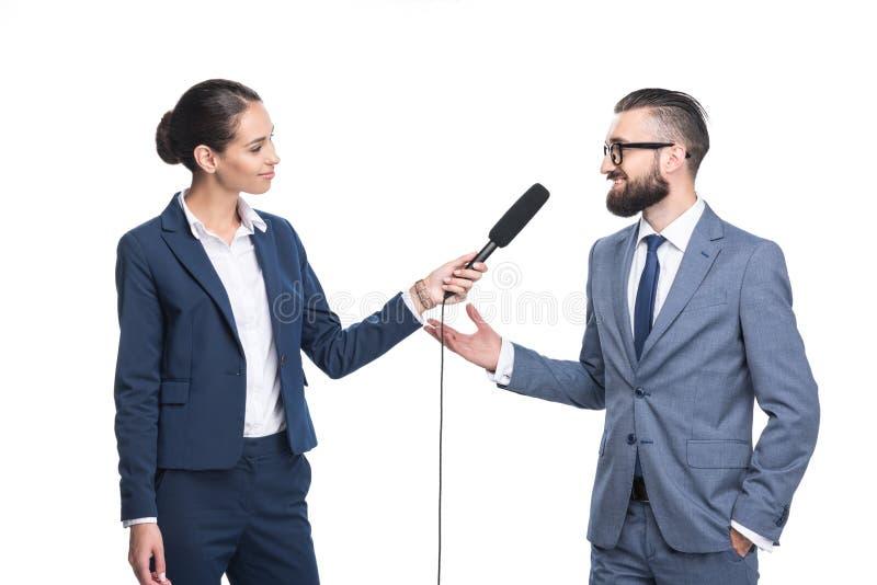 在衣服的微笑的女性新闻工作者采访的商人, 图库摄影