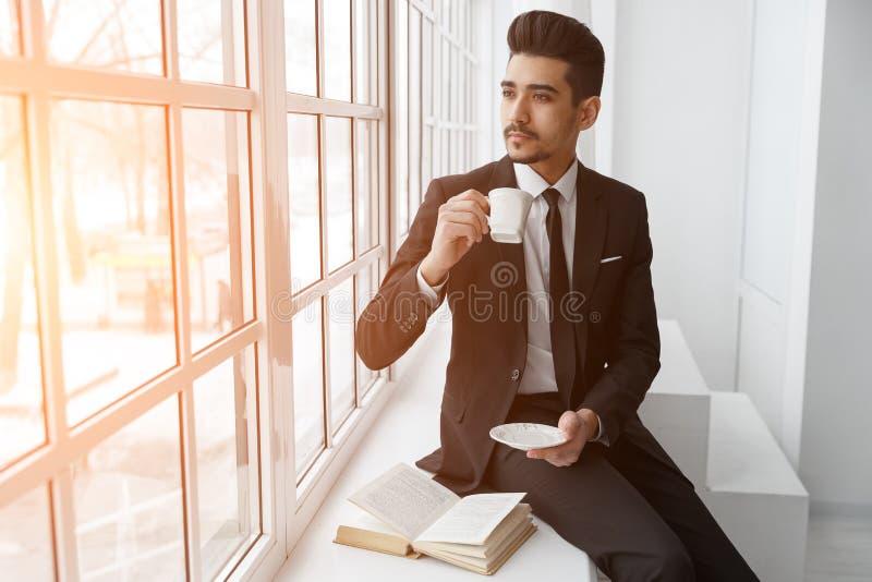 在衣服的想法的商人坐窗台和饮料咖啡 库存图片