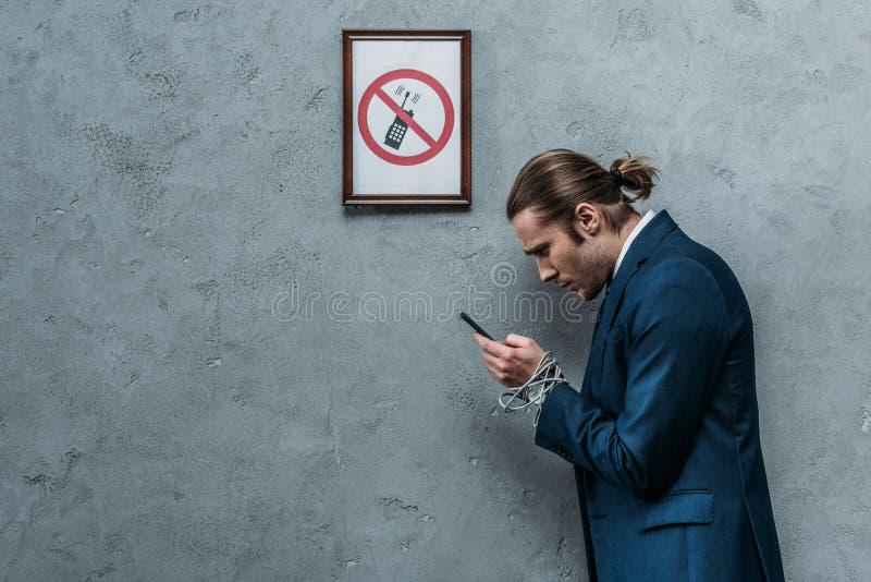 在衣服的沮丧的商人用手绑住与导线使用智能手机在有限的智能手机标志,电话下 库存图片