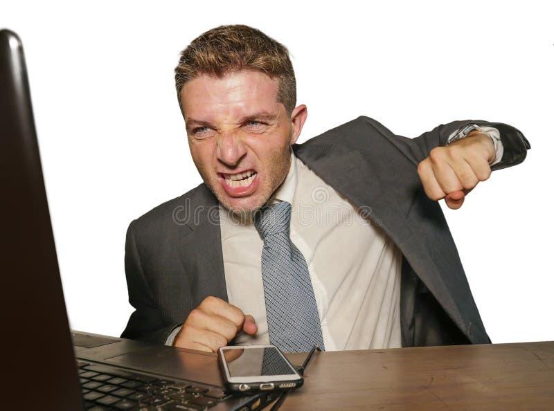 在衣服的生气和被淹没的运作在财政的办公桌猛击的手提电脑痛苦重音的商人和领带 免版税库存图片