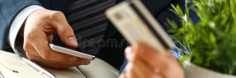 在衣服的男性胳膊拿着信用卡和电话 库存图片