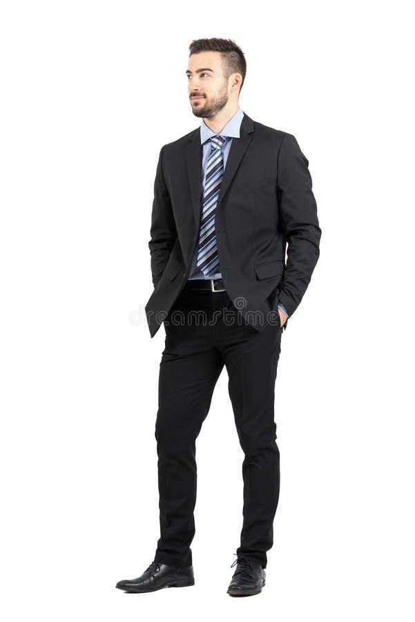 在衣服的看的商人用在口袋的手微笑和  免版税库存图片