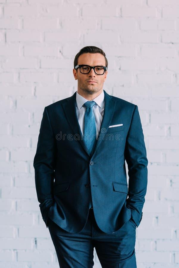 在衣服的确信的中间年迈的站立用在口袋和看的手的商人和镜片 免版税库存图片