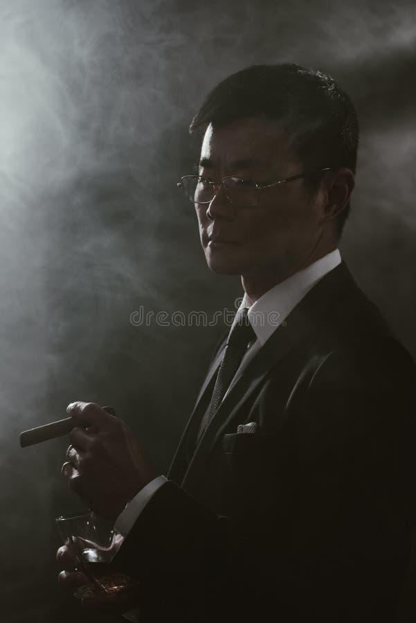 在衣服的确信的亚洲商人与杯威士忌酒抽烟的雪茄 库存照片