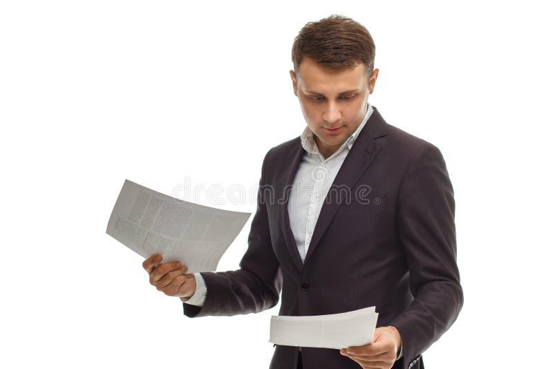 在衣服的英俊的商人与纸 免版税库存图片