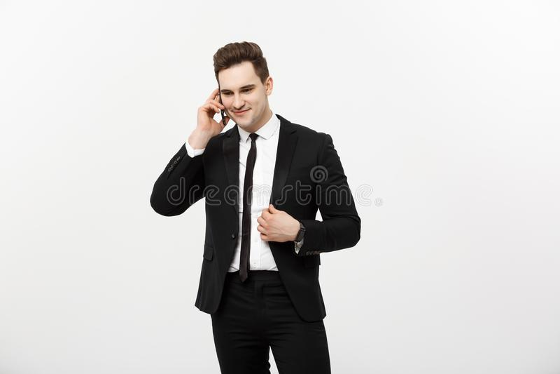 在衣服的英俊的商人说在被隔绝的白色背景的电话里 免版税库存图片