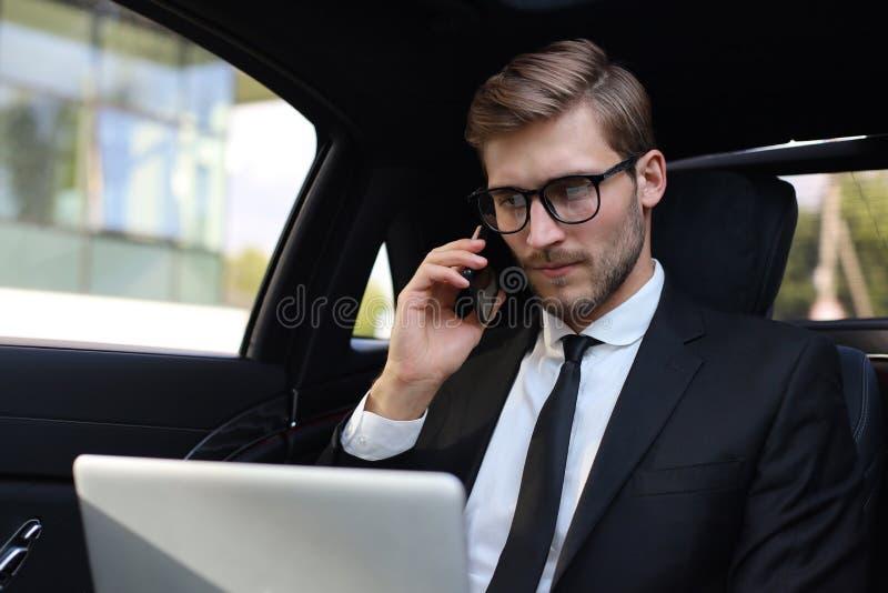 在衣服的英俊的确信的商人谈话在智能手机和工作使用膝上型计算机的,当坐在汽车时 免版税库存图片