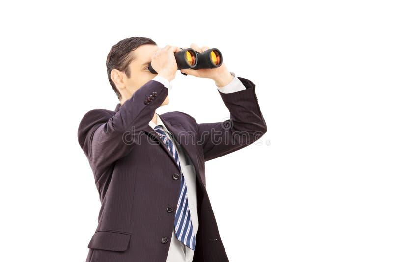 在衣服的年轻看通过双筒望远镜的商人和领带 免版税图库摄影