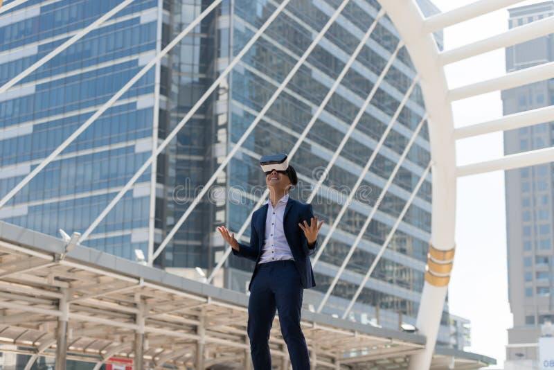 在衣服穿戴和虚拟现实玻璃的年轻亚洲商人 免版税图库摄影