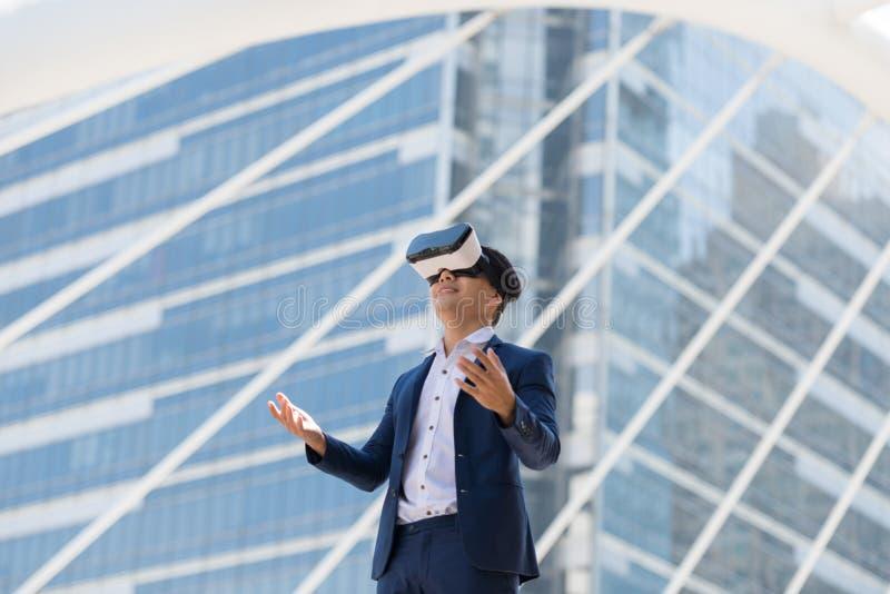 在衣服穿戴和虚拟现实玻璃的年轻亚洲商人 库存照片