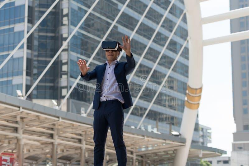 在衣服穿戴和虚拟现实玻璃的年轻亚洲商人 库存图片
