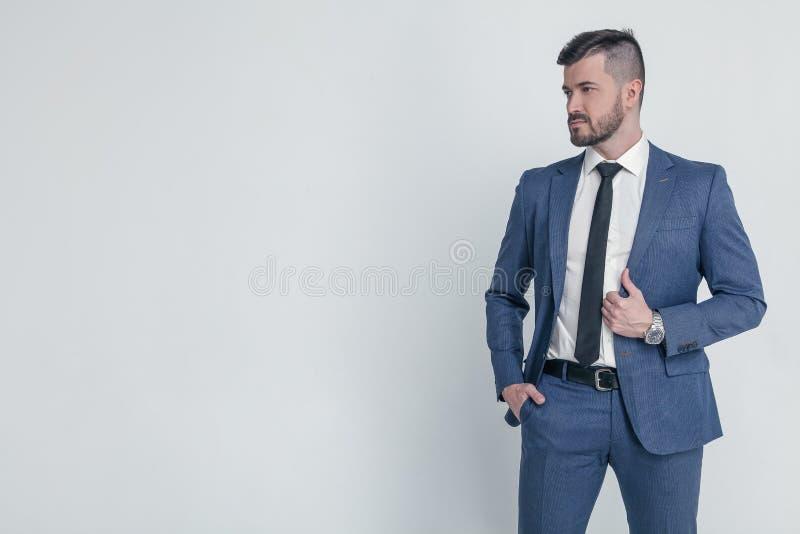 在衣服穿戴的一个迷人的成熟商人的画象摆在,当站立和看在灰色时的照相机 免版税库存图片