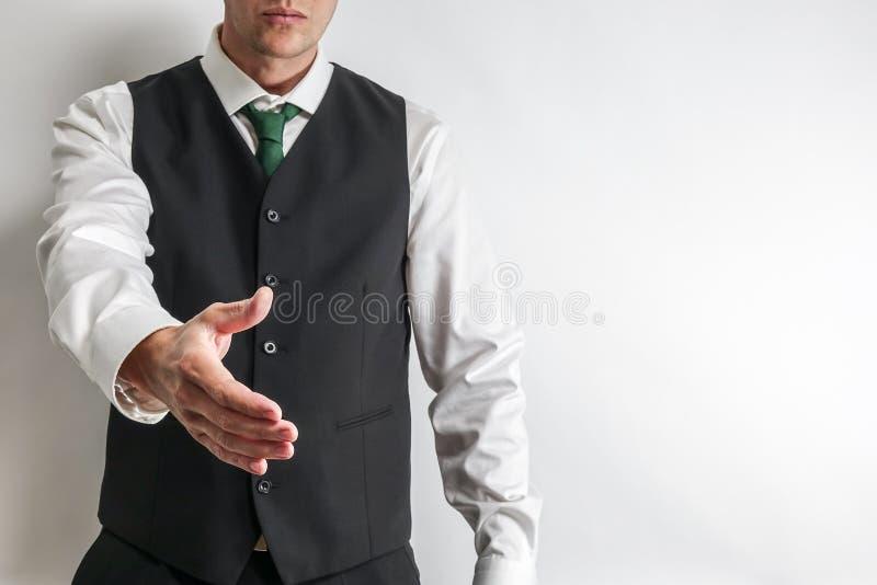 在衣服背心的商人有手提供援助对握手 免版税库存照片