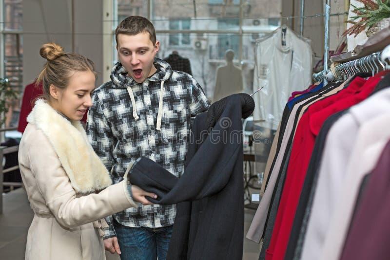 在衣物商店人的年轻夫妇激动 库存图片