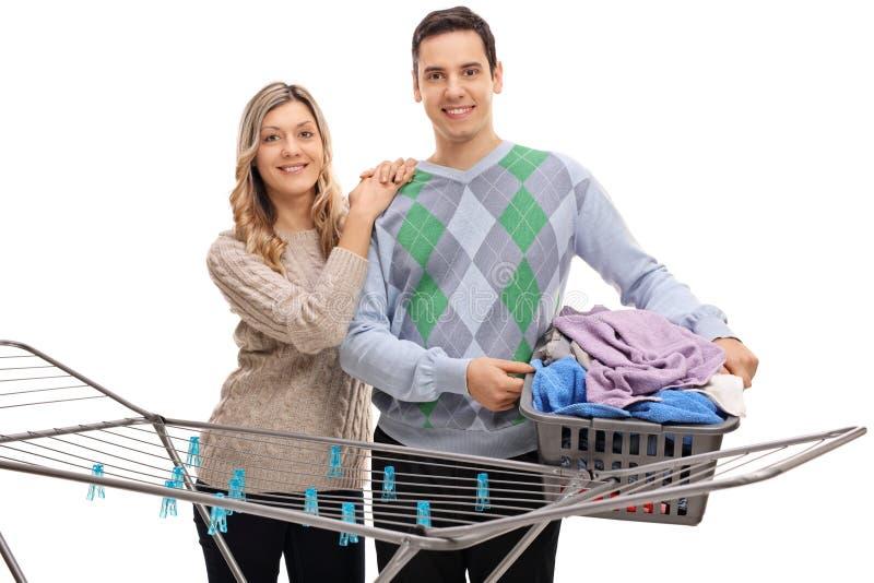 在衣物机架烘干机后的夫妇 免版税图库摄影