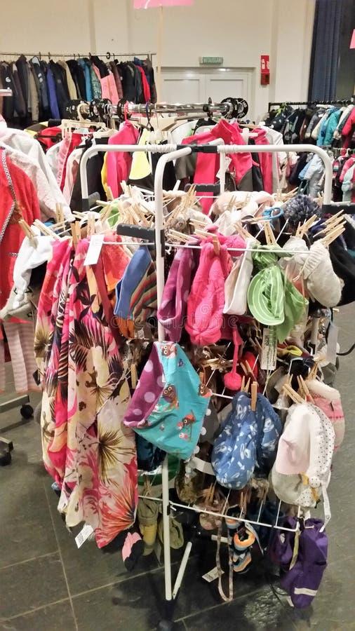 在衣裳的使用的衣裳在衣裳义卖市场站立 免版税库存照片