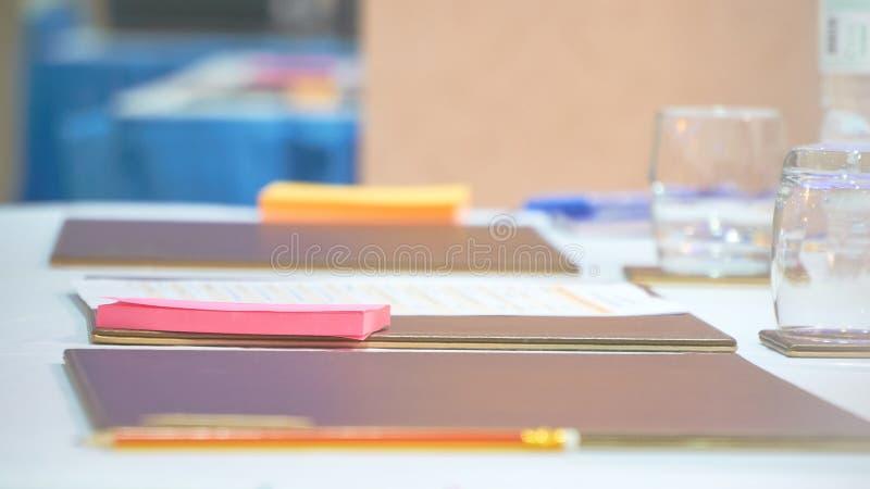 在表上的五颜六色的便条纸与玻璃和水瓶在候选会议地点 库存照片